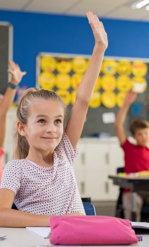Multiethnic group of young school children raising their hands to answer a question posed by the teacher. Group of elementary kids sitting in classroom and raising hands. Clever girl raising hand knowing the answer.
