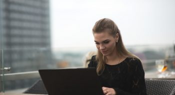Young adult woman using laptop and smartphone